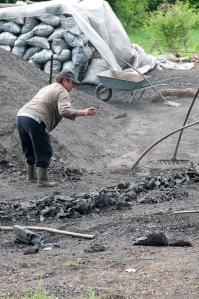 Mother tends the smoldering mound of charcoal