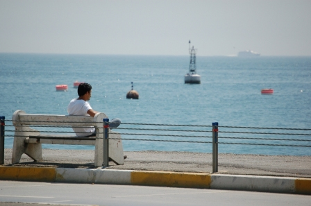 Man on bench looking out to sea