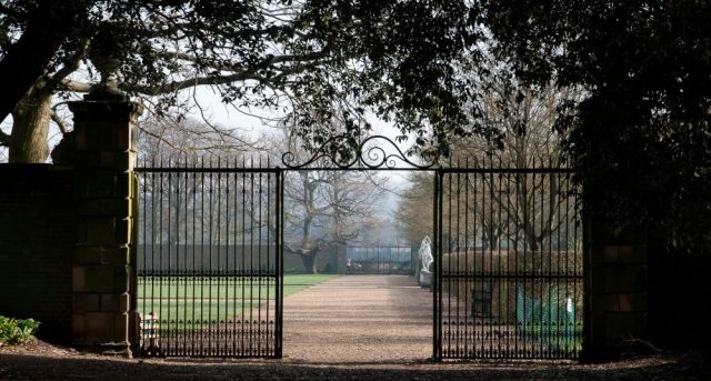 View of a long walk in Ham House garden, through the grill of a gate