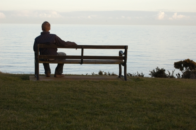 Figure seated on bench and looking out to sea