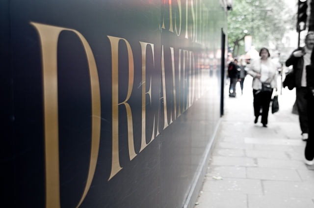 "Advertising hoarding reads ""dream"" as pedestrians walk past"