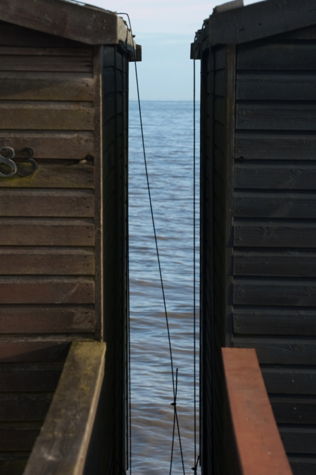 View of sea between beach huts